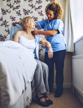 caregiver helping elder woman to dress