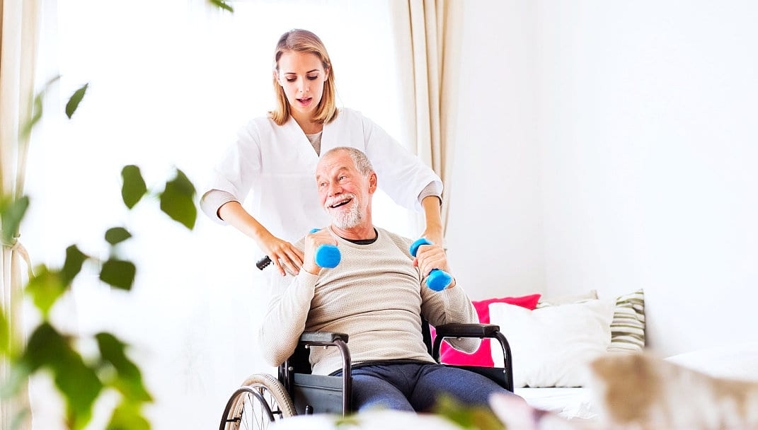 caregiver assisting elder man to lift weights