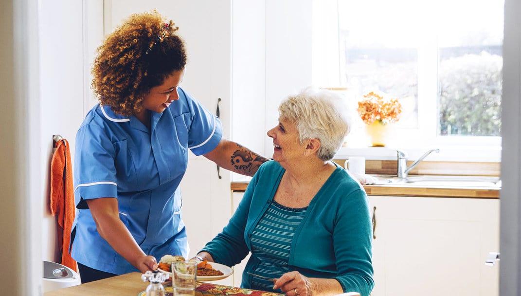 caregiver giving elder woman food