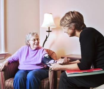 caregiver checks an elderly woman's blood pressure