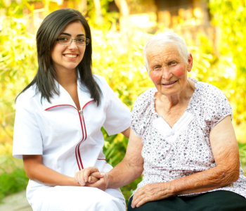 caregiver visiting an elderly women and holding her hands
