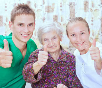 elderly woman and two nurse doing thumbs up