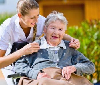 senior women sitting in wheelchair with nurse
