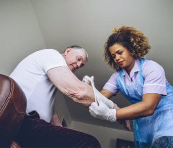 nurse putting a bandage on a senior mans arm